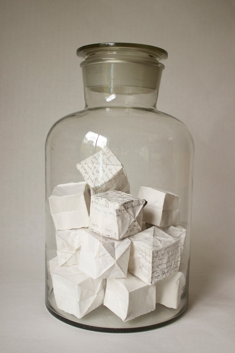 Dierdre Pearce under glass, 2014. Shell cast plaster, imprinted found text, found glass jar. Photograph Dierdre Pearce.