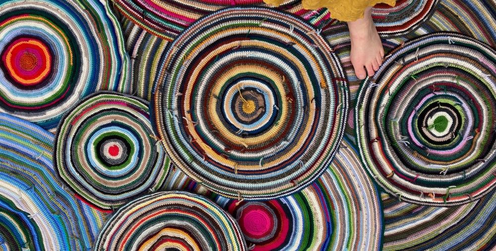 layers of colourful circular crochet rugs, with someone standing upper right in the image.