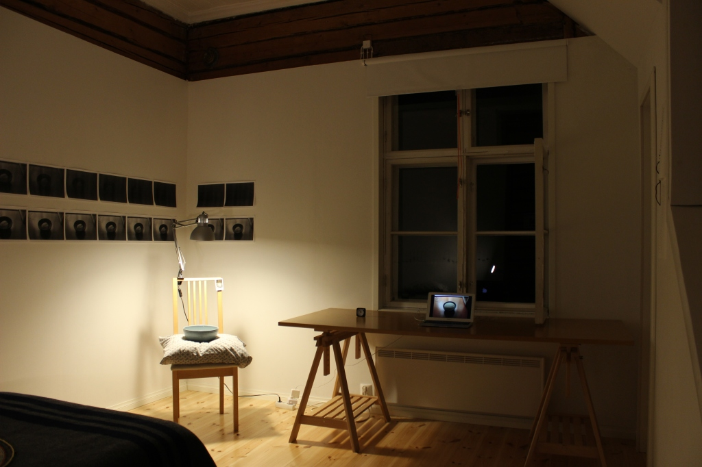 installation view of bread clock 2018, including chair with light, pillow and bowl of bread dough, computer screen with animation, clock and photocopies of images of dough rising in a bowl.